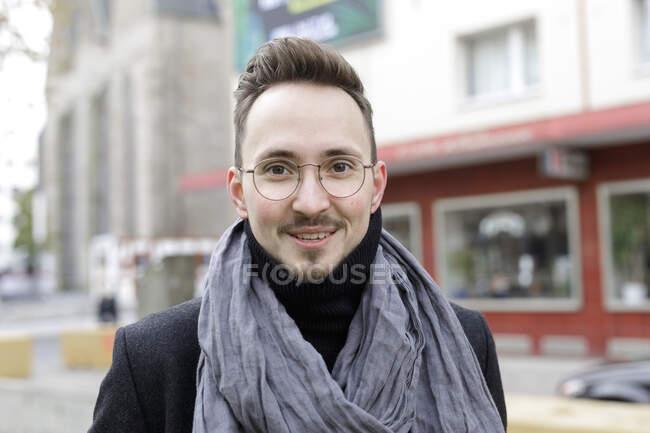 Ritratto di giovane sorridente in città in inverno — Foto stock