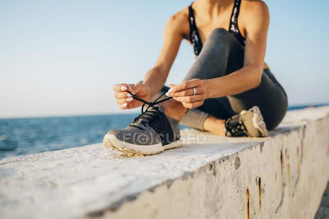 Спортсмен сидит на стене и завязывает кроссовки — стоковое фото
