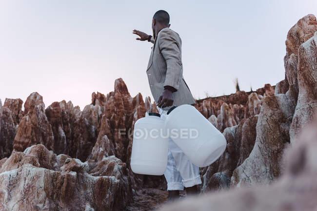 Joven sosteniendo vacío lata buscando agua en tierra estéril - foto de stock