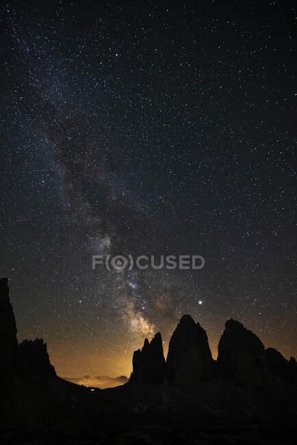 Vista panorámica de la silueta Tre Cime Di Lavaredo contra el campo estelar por la noche, Veneto, Italia - foto de stock