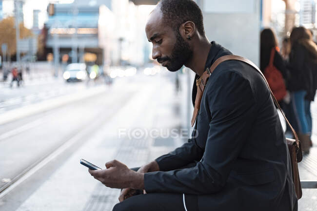 Young businessman sitting at tram stop looking at smartphone — Stock Photo
