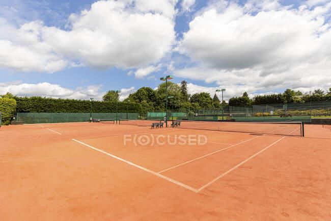 Quadra de tênis vazia com rede esportiva e marcações de canto contra o céu — Fotografia de Stock