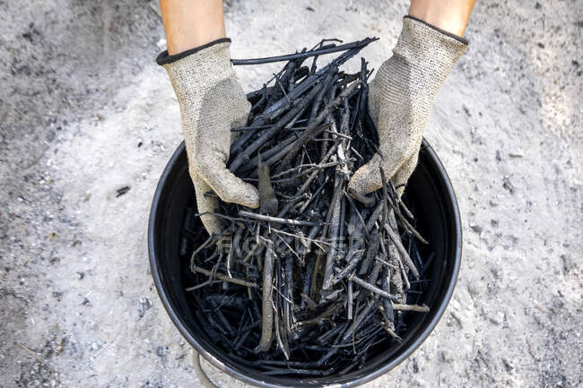 Hands holding self made charcoal outdoors — Stock Photo
