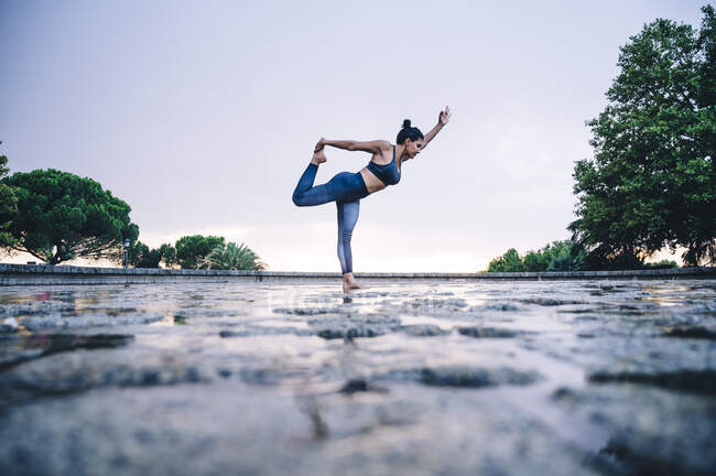 Женщина, практикующая йогу под дождем, позиция танцовщицы — стоковое фото