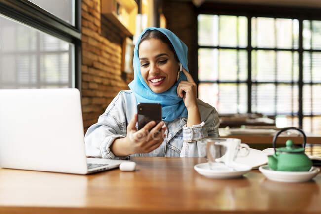 Безробітна жінка в бірюзовому хіджабі в кафе і працює — стокове фото