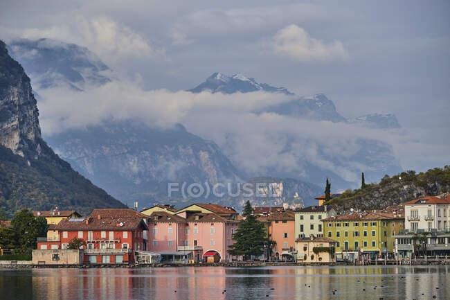 Italy, Trentino, Nago-Torbole, Coastal town on shore of Lake Garda with mountains in background — Stock Photo