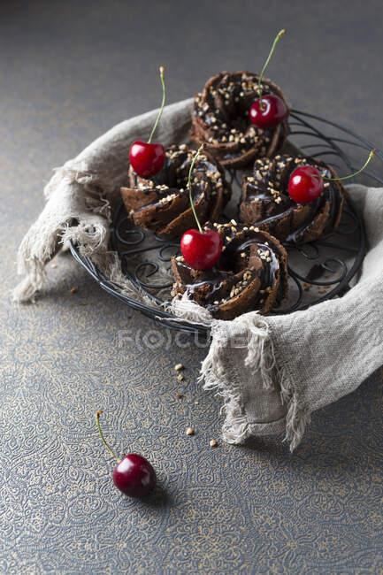 Basket of German minigugelhupf cakes with chocolate, brittle and cherries — Stock Photo
