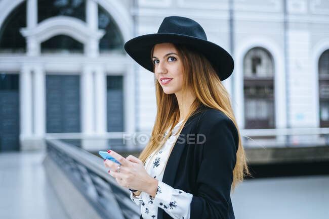 Smiling young woman with cell phone wearing a hat at train station — Stock Photo
