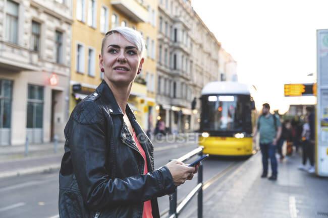 Retrato de mulher loira com smartphone em pé na parada de bonde, Berlim, Alemanha — Fotografia de Stock