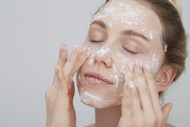 Retrato de una joven rubia con los ojos cerrados aplicando crema en su cara - foto de stock