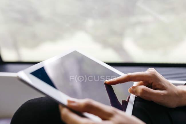 Mão de mulher usando um tablet enquanto viaja de trem — Fotografia de Stock