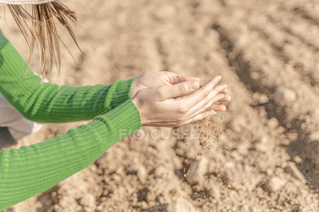 Soil trickling through hands of a woman — Stock Photo