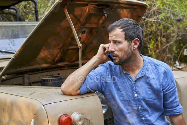 Hombre en el coche viejo con bonned abierto llamando a un mecánico - foto de stock
