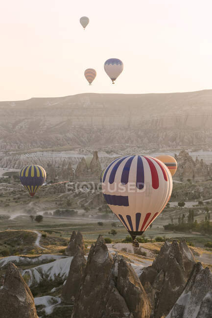 Colorful hot air balloons flying over land at Goreme National Park during sunset, Cappadocia, Turkey — Stock Photo