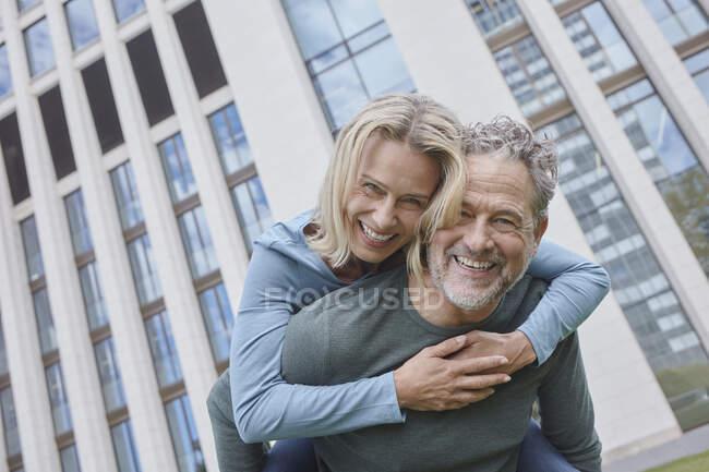 Щасливий дорослий чоловік носив у місті жінку - голубку. — стокове фото