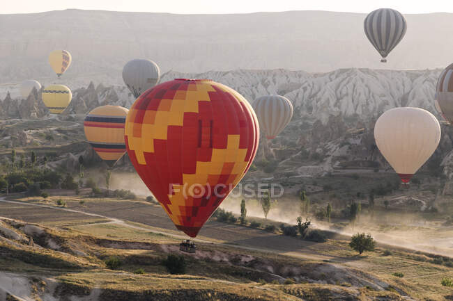 Багатокольорові повітряні кулі, що літають над сушею в національному парку Горем під час заходу сонця (Каппадокія, Туреччина). — стокове фото