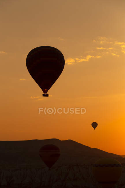 Silhouette hot air balloons flying over landscape in Cappadocia against sky at sunset, Turkey — Stock Photo