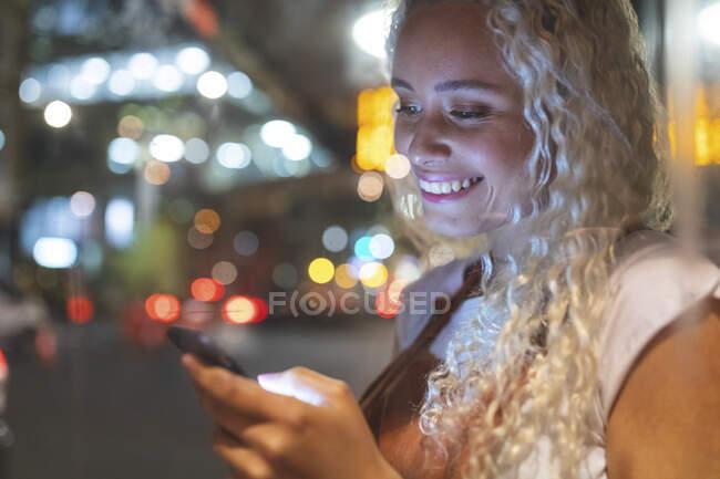 Молода жінка в Лондоні вночі дивиться на свій смартфон. — стокове фото