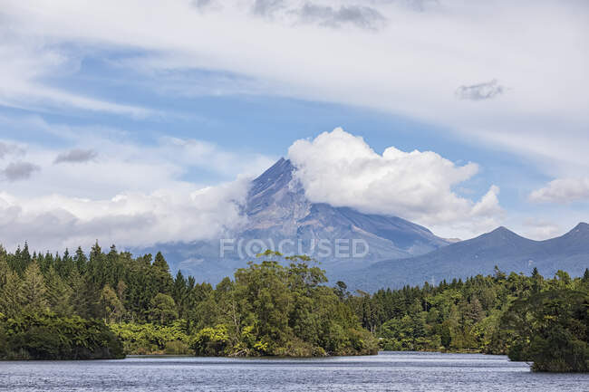 New Zealand, Scenic view of green forest surrounding Lake Mangamahoe with Mount Taranaki looming in background — Stock Photo