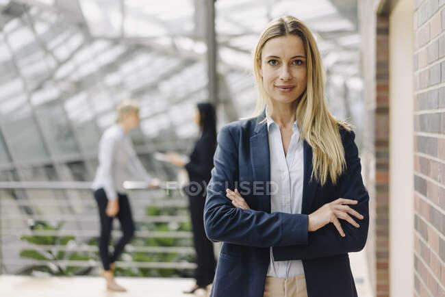 Портрет довіреної молодої бізнесменки в сучасному офісному будинку з колегами за походженням. — стокове фото