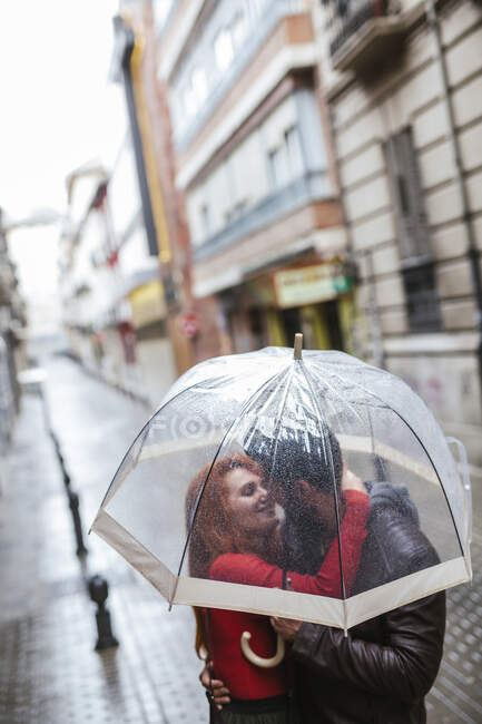 Couple in love kissing under transparent umbrella in the city — Stock Photo