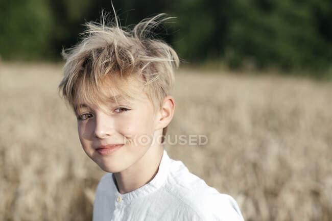 Retrato del niño rubio sonriente en un campo de avena - foto de stock