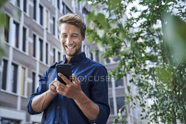 Happy young businessman using mobile phone in the city — Stock Photo