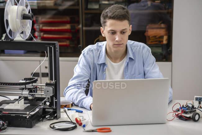 Étudiant configurant une imprimante 3D, en utilisant un ordinateur portable — Photo de stock