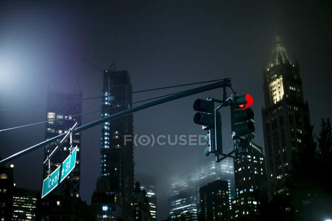Estados Unidos, Nueva York, Nueva York, semáforo colgado contra rascacielos iluminados por la noche - foto de stock