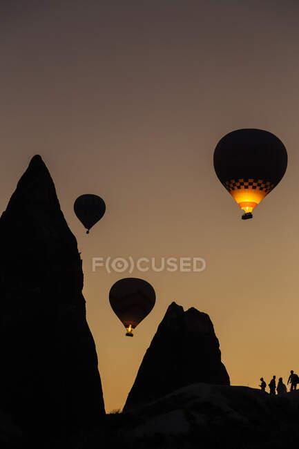 Під час заходу сонця (Каппадокія, Туреччина) над горами пролітають повітряні кулі Силуету. — стокове фото
