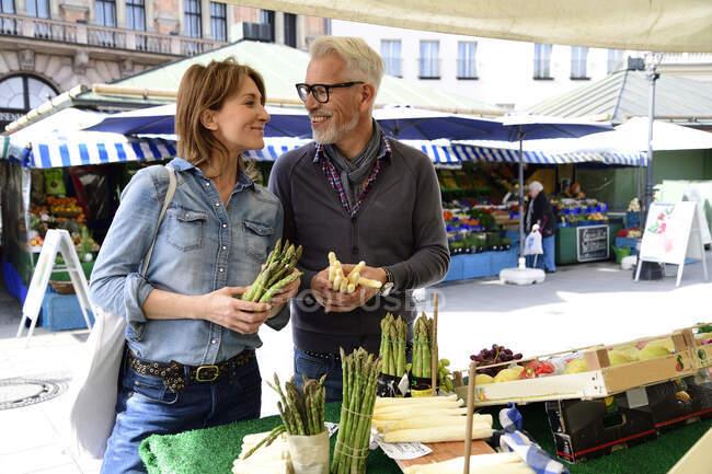 Casal maduro escolhendo espargos em uma banca de mercado — Fotografia de Stock