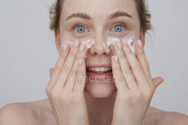 Retrato de una joven rubia que se aplica crema en la cara - foto de stock