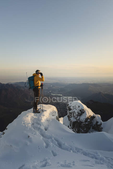 Mountaineer standing on top of a snowy mountain enjoying the view, Lecco, Italy — Stock Photo