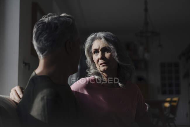 Серйозна старша пара сидить вдома на дивані в тіні. — стокове фото