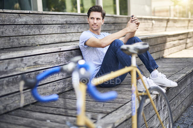 Portrait of man with racing bicycle sitting on bench having a rest — Stock Photo