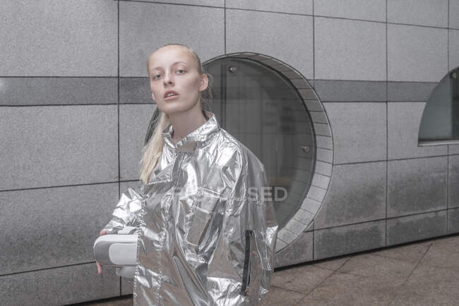 Girl in silver suit carrying VR goggles under her arm — Stock Photo