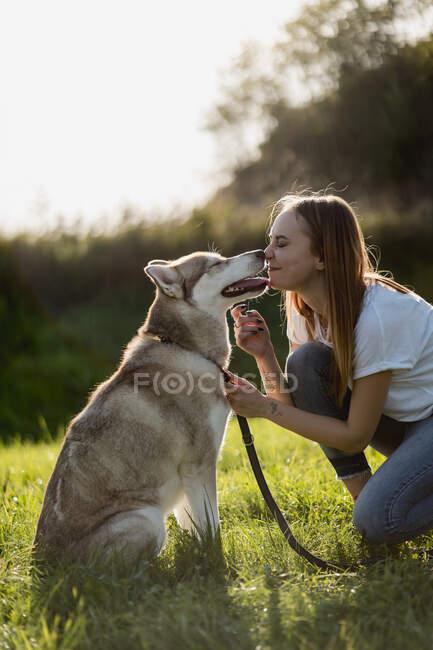 Giovane donna naso a naso con il suo cane su un prato — Foto stock