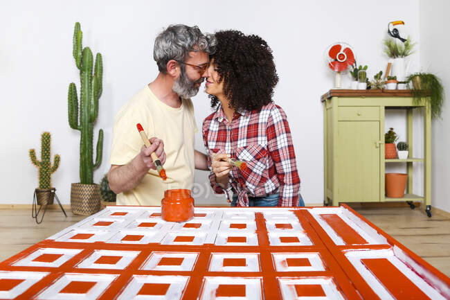 Couple painting furniture with brush at home — Stock Photo