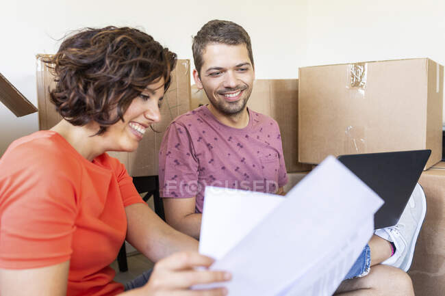 Happy couple in new home with documents and laptop — Stock Photo