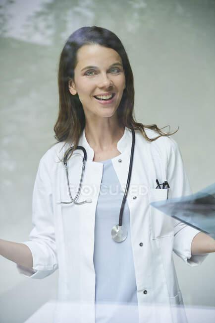 Retrato de la feliz doctora con imagen de rayos X detrás del cristal de la ventana - foto de stock