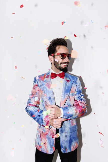 Uomo fresco ed elegante indossa un abito colorato e occhiali da sole sorridente a una festa circondata da coriandoli — Foto stock