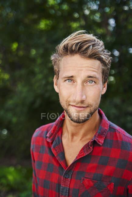Porträt eines selbstbewussten jungen Mannes im karierten Hemd — Stockfoto