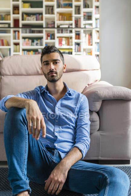 Портрет серйозного юнака, який сидить на підлозі у вітальні. — стокове фото