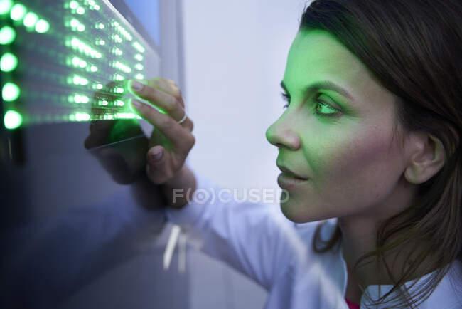 Зблизька жінка торкається зеленого сенсорного екрану. — стокове фото