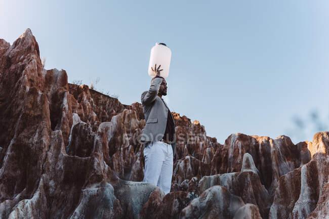 Молодий чоловік тримає порожню воду в пустині. — стокове фото