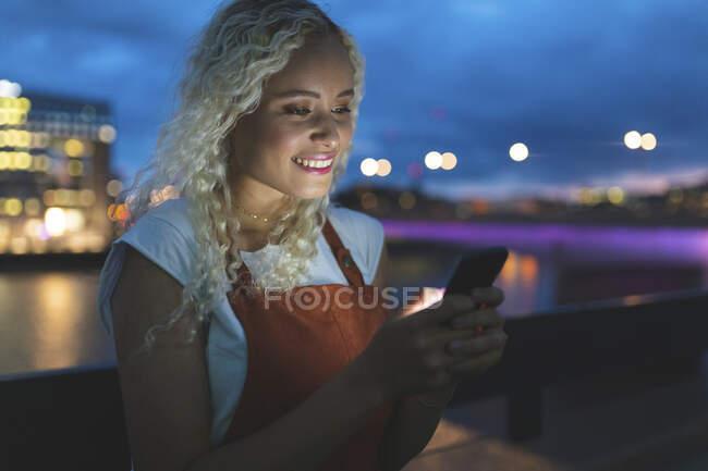 Молода жінка в місті на сутінках дивиться на свій смартфон. — стокове фото