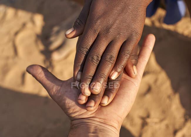 Manos negras estrechando manos blancas. Tribu Mucubal, Tchitundo Hulo, Angola - foto de stock