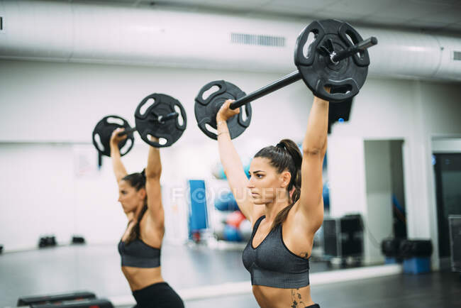 Twin sisters training with weights in gym — Stock Photo