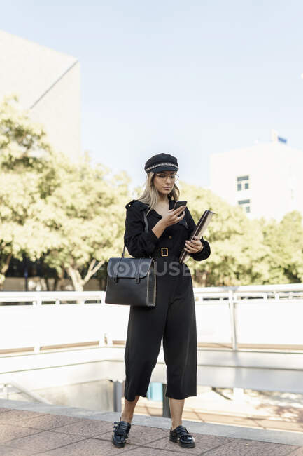 Young blond businesswoman wearing black hat and holding laptop bag and using smartphone — Stock Photo