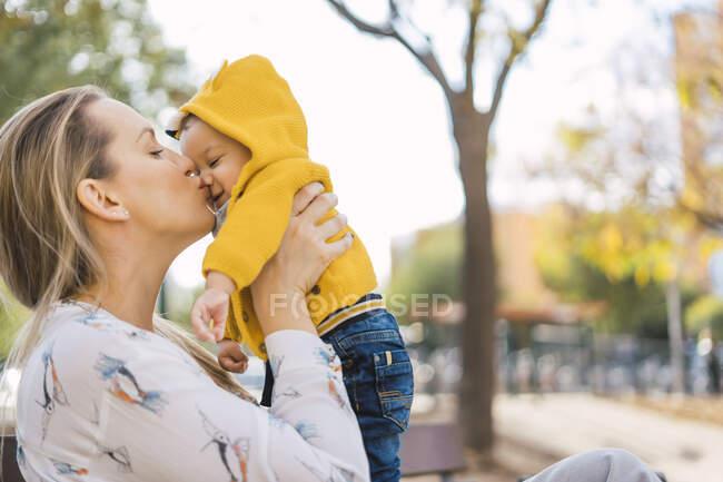 Мати цілує малюка в парку. — стокове фото